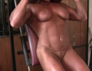 In the gym, Female bodybuilder Dana is doing biceps curls and posing in a sheer bodysuit