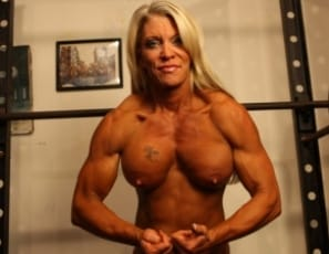 Female bodybuilder Ginger Martin is posing for you in the gym to show you how ripped her abs are