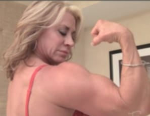 Female bodybuilder Lil Doll is nude in the bedroom after a long day, stretching the mature, vascular muscles