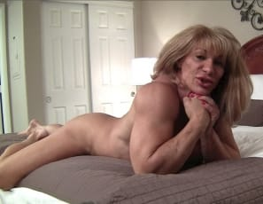 Female bodybuilder Wild Kat's posing in the Bedroom to show you how hard and lean she is