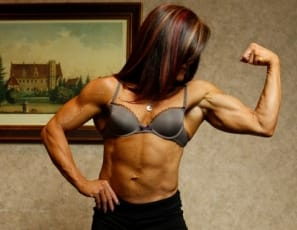 mature muscular female bodybuilder Tonya poses naked in the bedroom