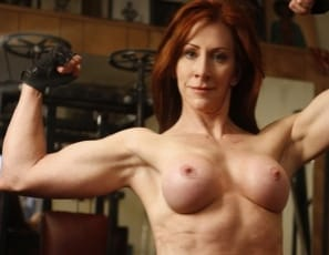 Mature female bodybuilder Vanna is posing in the gym, showing off the muscles in her pecs