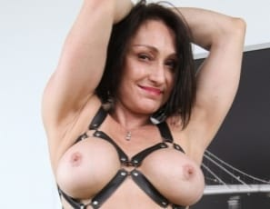 Female bodybuilder Jillian Foxxx harnesses the power of her muscles in a leather harness and high-heeled