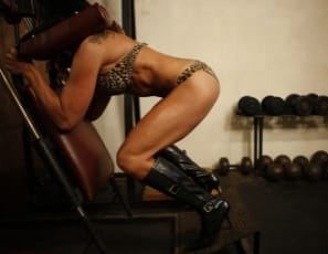 Willa's posing in the gym in shiny high-heeled boots, showing off her big biceps