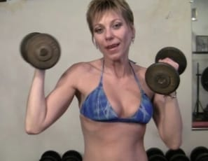 Gemma's working out and posing nude at the gym, and as she flexes her bicep muscle