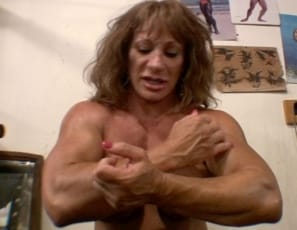 bodybuilder Wild Kat gives herself an oil massage, starting with her biceps and pecs