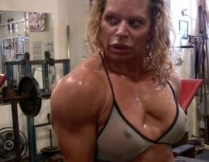 Bodybuilder Michelle Falsetta poses in the gym, stroking and massaging